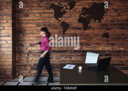 Blurred businesswoman walking to her desk and laptop computer in a spacious office with global map on the wall - Stock Photo