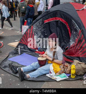 17th April 2019: Extinction Rebellion: Climate change activist playing her drum. Outside her tent in Oxford Circus, London, UK - Stock Photo
