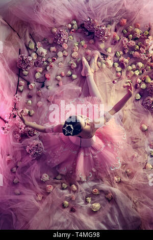 Looking for emotions. Top view of beautiful young woman in pink ballet tutu surrounded by flowers. Spring mood and tenderness in coral light. Art photo. Concept of spring, blossom, nature's awakening. - Stock Photo