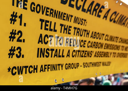London, UK - April 15, 2019: Extinction Rebellion campaigners yellow banner of three core demands for the government of United Kingdom, tell the truth - Stock Photo