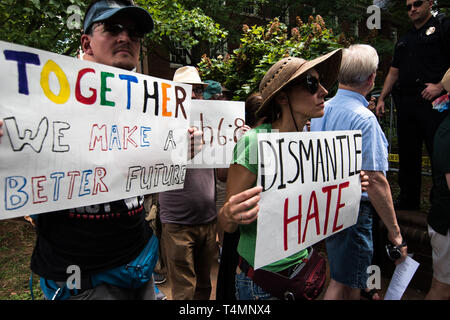 Peace Activists with Signs March in turn in front of Police  KKK Rally - Stock Photo