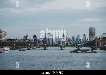 London, UK - April 13, 2019: Thames Clipper on River Thames, London skyline on the background, during blue hour. The Clippers are the fastest and most - Stock Photo