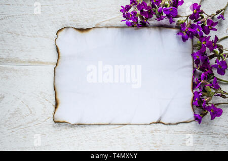 On white wooden boards, a white sheet of paper was burning on the edges, and purple flowers, leaving room for text. Concept background. - Stock Photo