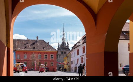 SIGHISOARA, ROMANIA - April 9, 2019: The Clock Tower in Sighisoara, seen through the arches at the entrance into the Citadel Square on a sunny day.