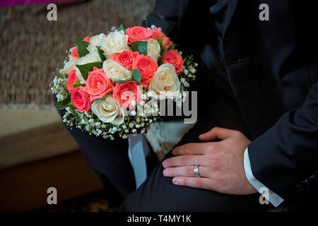 Groom holding wedding bouquet of white roses . bridal bouquet bride and groom on the Azerbaijan wedding . holding a beautiful bouquet of tender and - Stock Photo