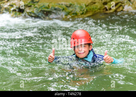Young boy swimming in water pool during canyoning tour - Stock Photo