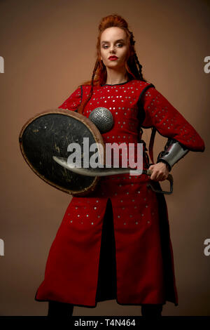 Brave, serious woman wearing as noble hero in red medieval tunic. Beautiful, charming model with ginger hair holding shield and dagger, posing in studio with weapon. - Stock Photo