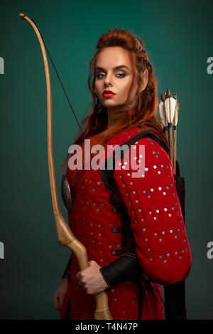 Beautiful female warrior holding bow in hand, with arrows behind back, wearing in red medieval tunic. Brave, serious woman with ginger hair, red lips and elf ear looking at camera, posing. - Stock Photo