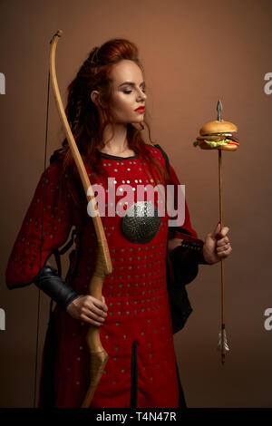 Medieval female warrior holding bow and arrow with hamburger, looking at tasty fast food burger. Gorgeous woman in red tunic with weapon posing and standing in studio. - Stock Photo