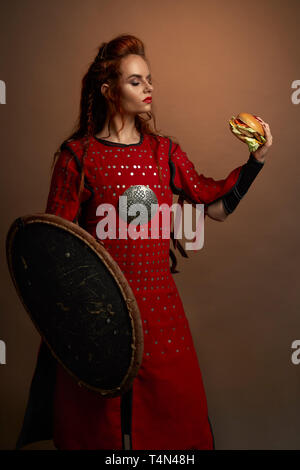 Beautiful woman warrior holding delicious hamburger in hand, looking at it. Serious, brave model wearing in medieval red dress, holding shield, standing and posing. - Stock Photo
