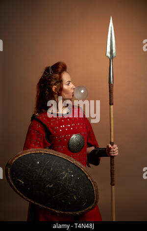 Brave female warrior wearing in red medieval costume blowing big bubble from chewing gum. Beautiful, gorgeous woman with red lips posing in studio, holding shield and big spear. - Stock Photo