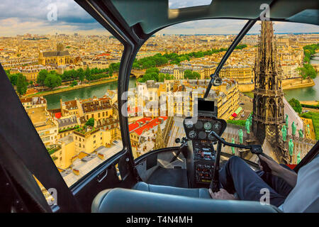 Helicopter cockpit flying on Notre Dame church with its spire and on skyline of Paris, French capital, Europe. Scenic flight over Paris cityscape. - Stock Photo