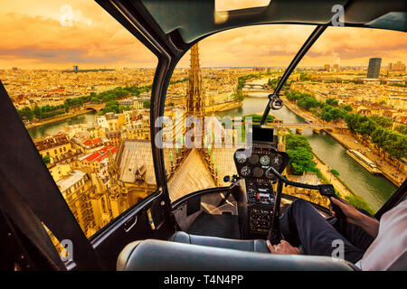 Helicopter cockpit flying at sunset on Notre Dame de Paris cathedral and on skyline of Paris, French capital, Europe. Scenic flight over Paris - Stock Photo