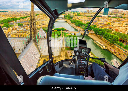 Helicopter flying on the roof of Notre Dame church spotting its spire, in Paris panorama, French capital, Europe. Scenic flight over Paris cityscape. - Stock Photo