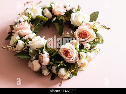 Fake pink rose wreath on a pink background with fake leaves - close up - Stock Photo