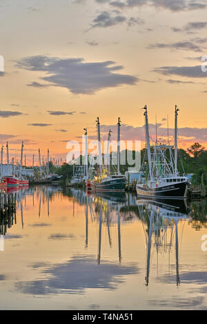 Commercial fishing boats and shrimp boats tied up at sunset in Bayou La Batre Alabama, USA. - Stock Photo