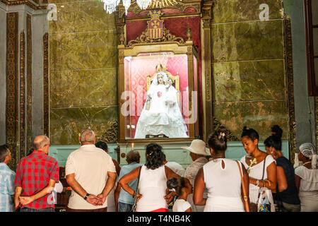 Havana, Cuba - 25 July 2018: People praying, lighting candles and leaving flowers to Madonna in a Havana Cuba Church. - Stock Photo