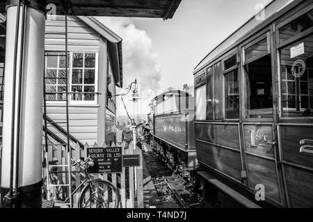 Black & white morning scene on vintage steam railway line, UK. Vintage steam train departure, Bewdley station; signalman in signal box watching train. - Stock Photo