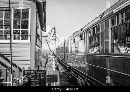 Railway signalman on SVR heritage line looks out of signal box window to greet children waving from inside vintage steam train leaving the station. - Stock Photo