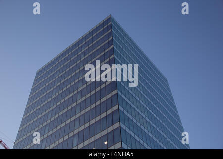 Madrid, Spain - 04 12 2019: Office building with glass facade towards blue sky - Stock Photo