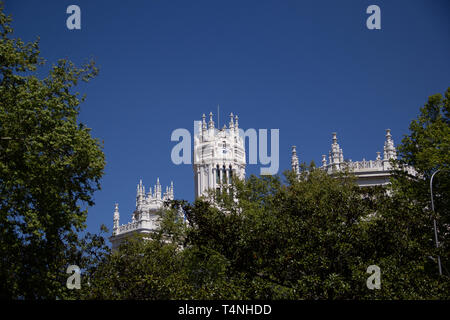 Madrid, Spain - 04 12 2019: Main post office building behind green trees - Stock Photo