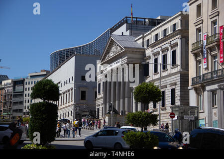 Madrid, Spain - 04 12 2019: National Congress building from the side behind round cut green trees - Stock Photo