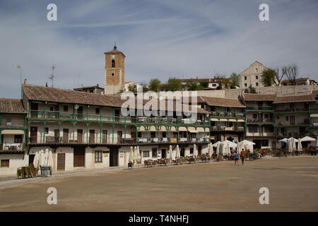 Chinchon, Spain - 04 14 2019: Buildings with green balconies and the clock tower in the background - Stock Photo