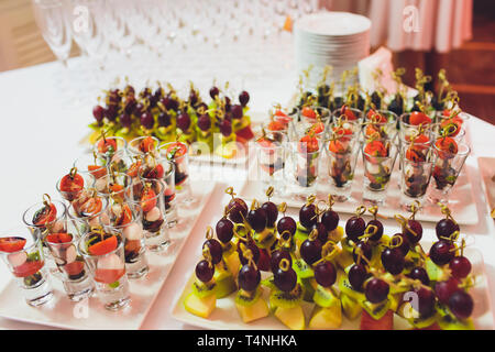 Beautifully decorated catering banquet table with burgers, profiteroles, salads and cold snacks. Variety of tasty delicious snacks on the table. - Stock Photo