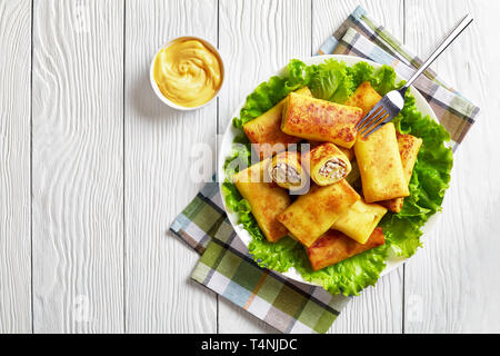 Savory crepe rolls with ground chicken meat and mushrooms filling served on a bad of fresh lettuce leaves on a white plate on a wooden table with chee - Stock Photo
