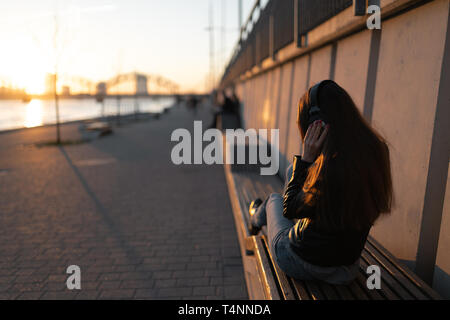 Young woman listens to music in closed headphones through her phone wearing a leather jacket and jeans at a sunset near river Daugava - Stock Photo