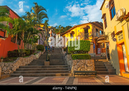 Cityscape with people walking down the famous 444 steps of the Santa Ana Hill, a place with bars and restaurants, at sunset in Guayaquil, Ecuador. - Stock Photo