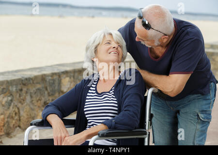 elderly man talking affectionately to his wheelchair bound wife - Stock Photo