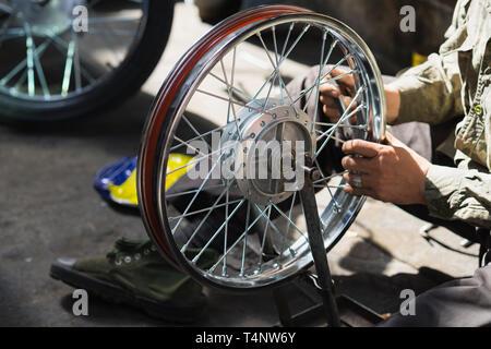 Motorbike wheel is repairing by Asian man on street - Stock Photo