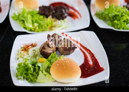 Grilled steak of lamb meat cut on slice with round bread, salad, oil, sauce - Stock Photo