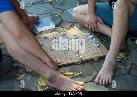 Closeup two old men playing Chinese chess on Hanoi sidewalk, Vietnam. Focus on chessboard - Stock Photo