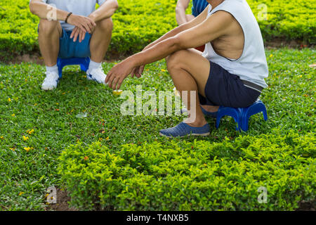 Old men sitting on grass in park having chatting in Asia - Stock Photo