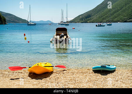 View of the beach on a sunny day with a yellow kayak in the foreground - Stock Photo