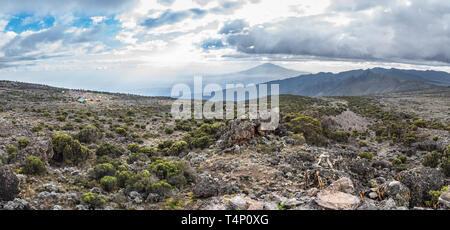 Panoramic view of the Shira Cave Camp site on the Machame hiking route on Mt Kilimanjaro, Tanzania. Mount Meru is behind sun rays in the background. - Stock Photo