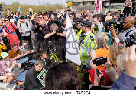 Extinction Rebellion activists occupy Waterloo Bridge for the third day on 17th April. Metropolitan Police officers prepare to arrest demonstrators. - Stock Photo