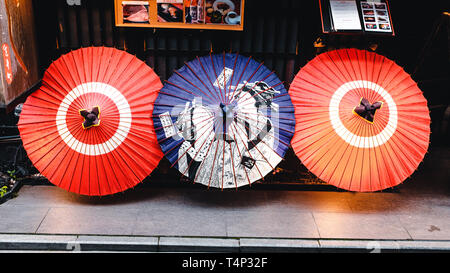 Three Umbrellas in the Streets of Kyoto, Japan - Stock Photo