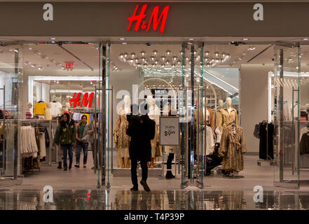 Back view of semi-silhouetted man carrying toddler boy, walking into H&M clothing shop/store at the mall in the new Hudson Yards complex that had opened earlier that month, the highly reflective floor outside the doorway beneath his feet, while shoppers inside browse, or walk toward the exit. Hudson Yards, New York's newest neighborhood, debuted 15 March 2019, to controversy about whether it was too elitist. According to a company press release, the development 'brings together for the first time the West Side and the neighboring districts of Chelsea and Hell's Kitchen'. - Stock Photo