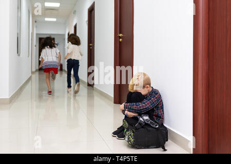 Crying little boy sitting on school floor with hands on knees and head between his legs suffering an act of bullying while two girls run away - Stock Photo