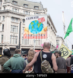 London, UK, April 17 2019 - Protesters hold a banner and an Extinction Rebellion flag at a climate change protest outside Oxford Circus underground st - Stock Photo