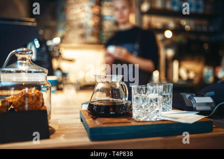Glasses with black coffee and filtered water, male barista at cafe or bar counter on background. Professional espresso preparation by bartender in caf - Stock Photo