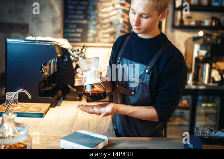 Young male barista makes fresh espresso at cafe counter. Barman works in cafeteria, bartender prepares black coffee - Stock Photo