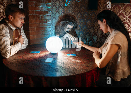 Female foreteller guessing by hand over a crystal ball