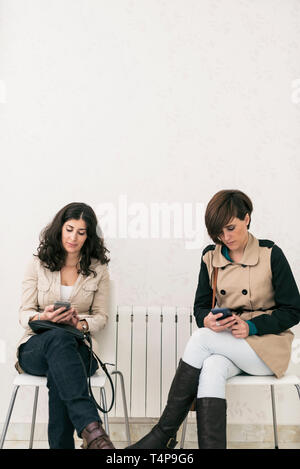 Two women in waiting room looking smartphone serious, sitting on chair - Stock Photo