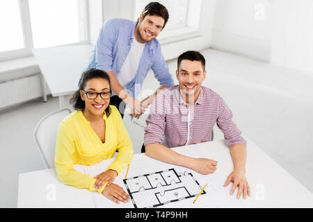 business, architecture and people concept - creative team of architects or interior designers with blueprint working at office - Stock Photo