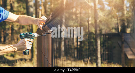 fencing - worker installing metal wire mesh fence panel - Stock Photo