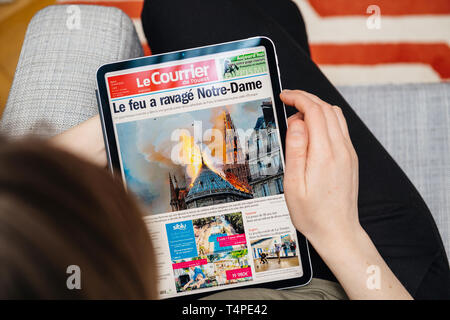 Paris, France - Apr 15, 2019: Woman reading Le Courrier de l'Ouest on iPad Pro Apple News Plus digital newspaper featuring breaking news on cover French Notre-Dame Cathedral on fire causing damages  - Stock Photo